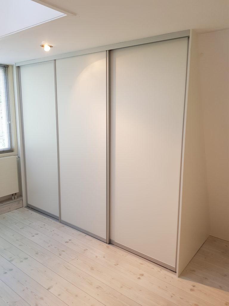 Schuifdeurkast onder een schuine wand 3 witte deuren aluminium omlijsting