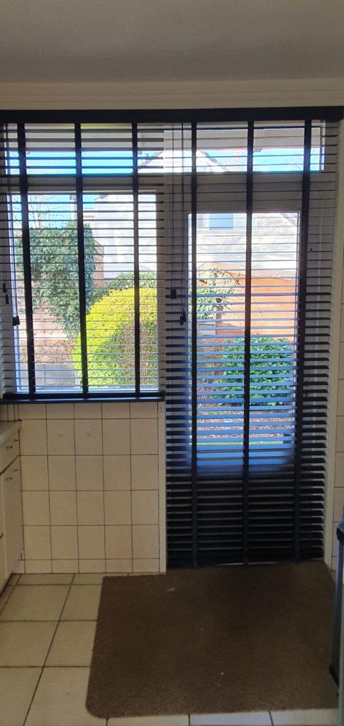 Houten jaloezien voor een deur en een raam
